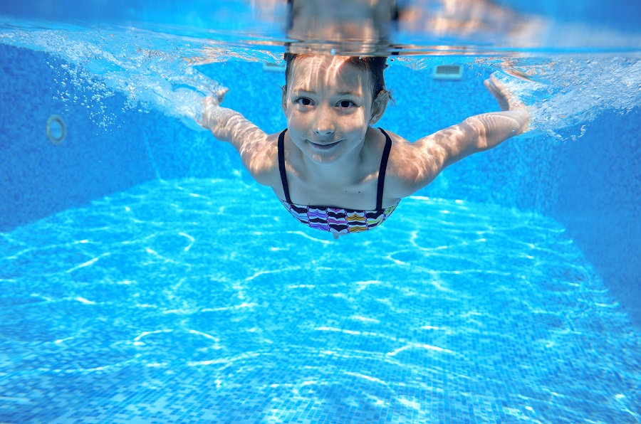 Kid swims in pool underwater, girl swimming having fun